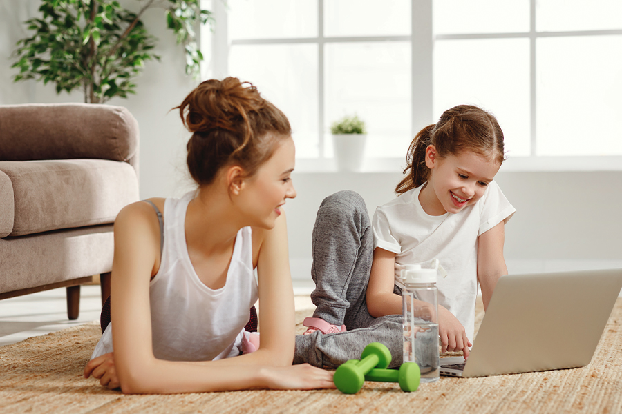 Employee Benefits - Cheerful Woman with Daughter Using Laptop During Exercise Training at Home